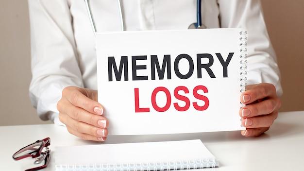 Karta utraty pamięci w rękach lekarza. ręce lekarza kartkę papieru z tekstem utrata pamięci, koncepcja medyczna.