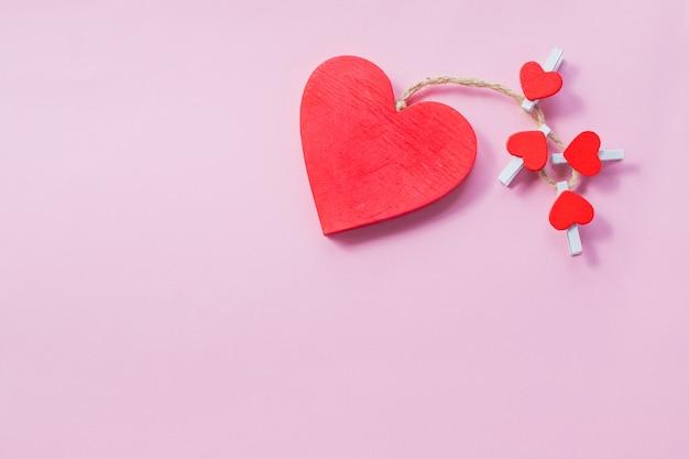 Karta walentynkowa. drewniane czerwone serca na białym tle na różowym tle. koncepcja szczęśliwy walentynki. świąteczna pocztówka. koncepcja miłości na dzień matki i walentynki. miejsce