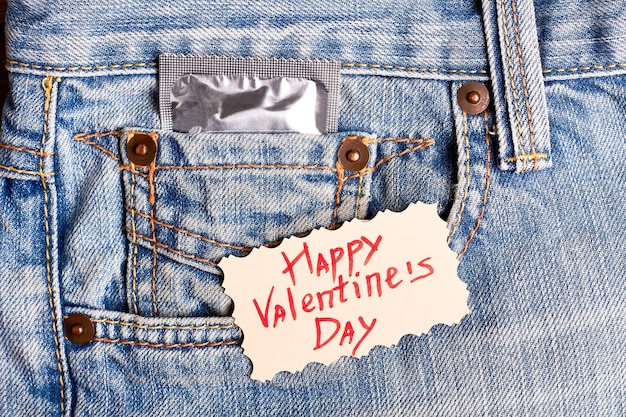 Karta walentynkowa i prezerwatywa. kartkę z życzeniami na denim. bądź bezpieczny podczas świętowania.