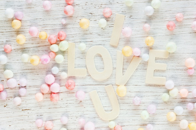 Karta walentynkowa z tekstem i love u i stertą koralików w stonowanym drewnianym, słodkim pastelowym kolorze.