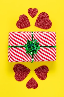 Karta walentynkowa. zapakowany prezent. minimalistyczny design. świąteczny prezent i czerwone serca na żółtym tle papieru, romantyczne symboliczne świętowanie miłości i uczucia.