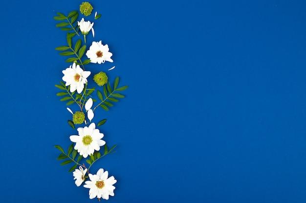Karta z białymi kwiatami i zielonymi liśćmi na urodziny, dzień matki lub ślub. niebieska przestrzeń papieru.