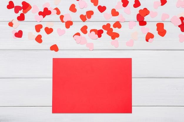Karta z czerwonym sercem nad nim na białym drewnie