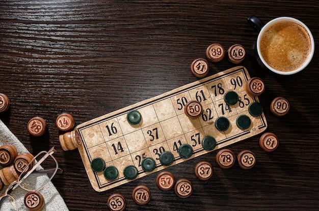 Karta z numerami i beczkami lotto z bliska. kawa i szklanki na ciemnym stole