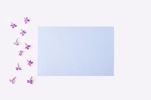 Karta z pozdrowieniami zaproszenie kompozycja płaskich kwiatów leżących na twój napis.
