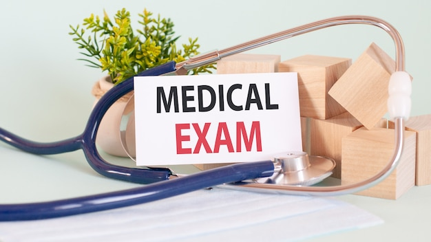 Karta z tekstem badanie lekarskie, pojęcie medyczne. drewniane klocki, stetoskop, kwiaty w tle