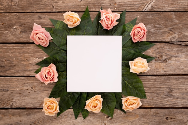 Karta zaproszenie na ślub z różami na starym brązowym drewnie.