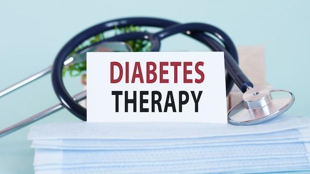 Karta ze słowami terapii cukrzycy, stetoskopem, maskami na twarz i kwiatem na stole.