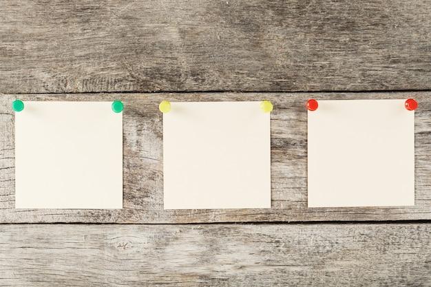 Karteczki samoprzylepne z szpilkami w rzędzie na drewnianej powierzchni
