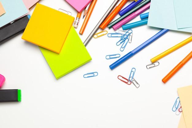 Karteczki ze znacznikami, kolorowe długopisy, spinacze na stole
