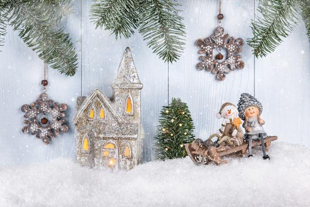 Kartka bożonarodzeniowa i noworoczna z uśmiechniętymi figurkami na saniach i innymi dekoracjami