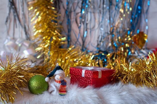Kartka bożonarodzeniowa z bałwanem w świątecznych dekoracjach. ozdoby świąteczne i czerwone pudełko. selektywne skupienie na pierwszym planie.