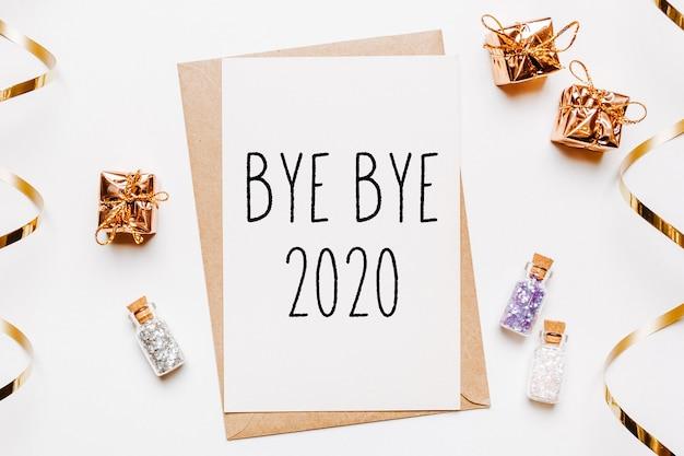 Kartka do widzenia 2020 z kopertą, prezentami i złotymi brokatowymi gwiazdkami na białej ścianie.