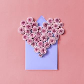 Kartka gratulacyjna z kwiatami serca i kopertą rękodzieła na pastelowym tle. widok z góry.