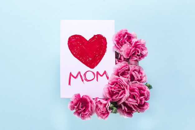 Kartka na dzień matki z czerwonym sercem napisanym na niej z różowymi kwiatami wokół i jasnoniebieskim tłem