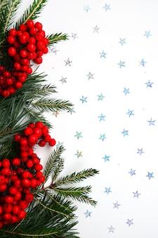 Kartka noworoczna i świąteczna zielona choinka i sosna z jagodami czerwonej jarzębiny na białym