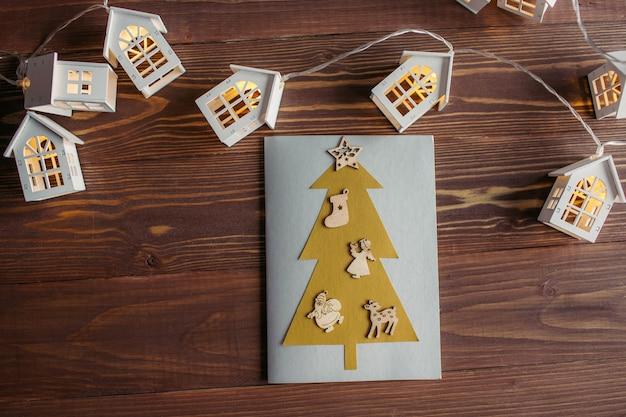 Kartka noworoczna wykonana przez dziecko z kolorowego papieru i drewnianych dekoracji
