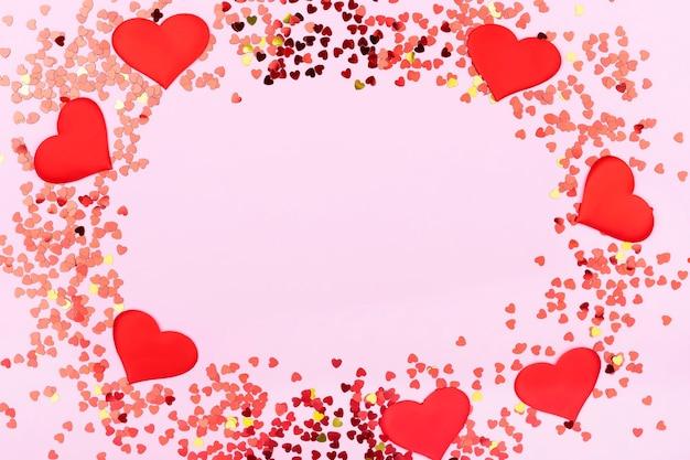 Kartka ozdobiona czerwonymi wzorami serduszka, walentynki. karty okolicznościowe na różowym tle z miejscem na tekst. transparent.
