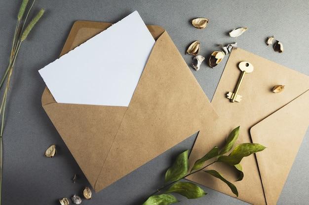 Kartka papieru w kopercie z gałęziami na szarym tle