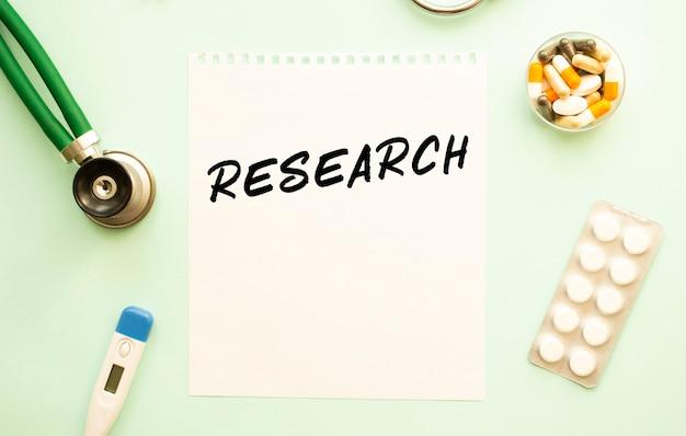 Kartka papieru z tekstem stetoskop badawczy i lekarstwa