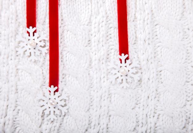 Kartka świąteczna, białe tło z dzianiny. zabawki, płatki śniegu na czerwonej wstążce. widok z góry. skopiuj miejsce