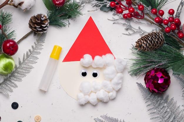 Kartka świąteczna diy krok po kroku. z kolorowego papieru i bawełny. przyklej trójkąt do koła podłogi. następnie przyklej waciki i oczy.
