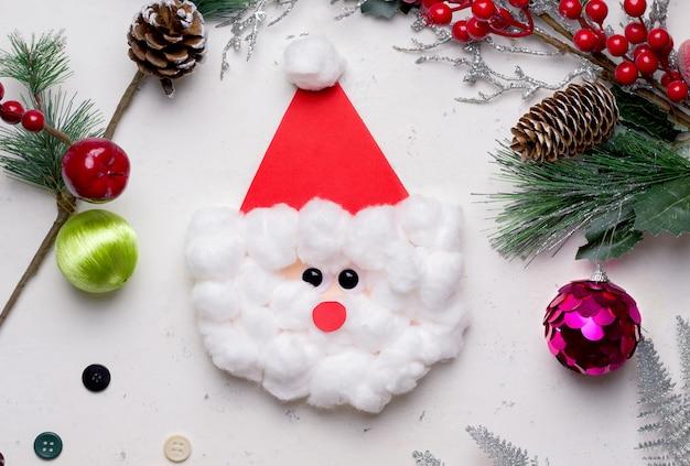Kartka świąteczna diy krok po kroku. z kolorowego papieru i bawełny. to gotowa kartka okolicznościowa w kształcie świętego mikołaja na zewnątrz.