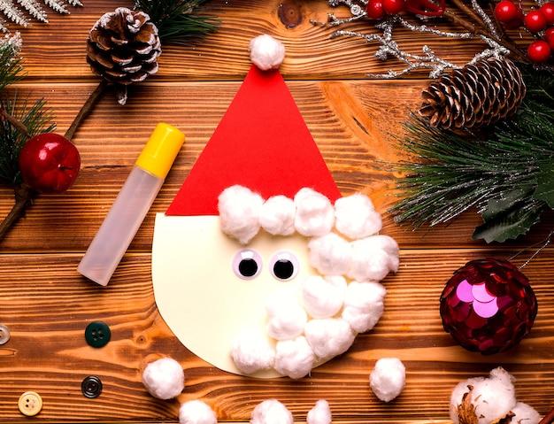 Kartka świąteczna diy krok po kroku. z kolorowego papieru i waty na drewnianym stole. krok trzeci