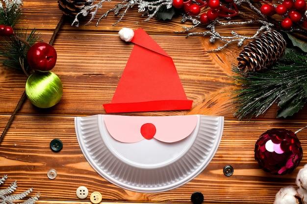 Kartka świąteczna diy krok po kroku. z plastikowego talerza, kolorowego papieru i waty.