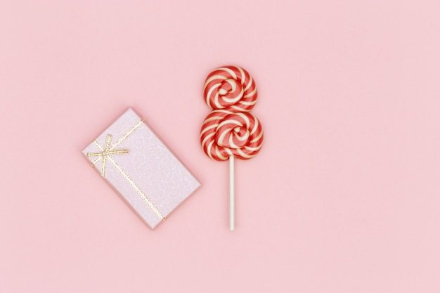 Kartka świąteczna dla kobiet, gratulacje 8 marca. jasnoczerwony lizak i pudełko na różowym tle.