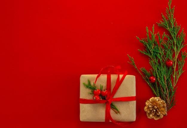 Kartka świąteczna i noworoczna w tle świerkowe prezenty na czerwonym tle płaskie miejsce do kopiowania