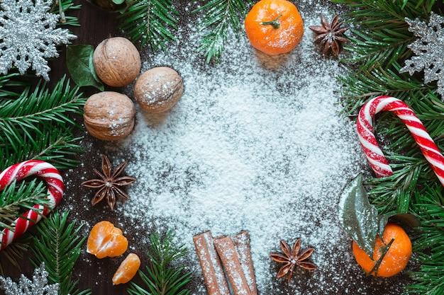 Kartka świąteczna. kompozycja noworoczna mandarynki, orzechy, świerk, cukierki