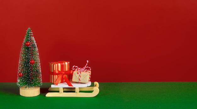 Kartka świąteczna lub noworoczna. dekoracyjne jodły, prezenty i sanki na czerwonym, zielonym tle. tło wakacje. skopiuj miejsce