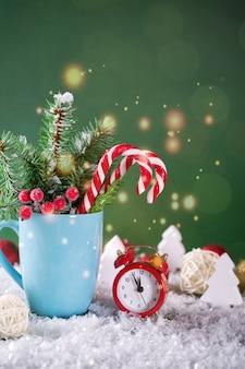 Kartka świąteczna lub noworoczna. kubek z jodłami, pędami cukierków i czerwonym zegarem.