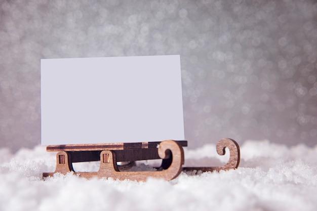 Kartka świąteczna na saniach na śniegu. tło uroczysty brokat