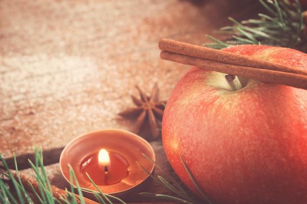 Kartka świąteczna. świeca jabłkowa i laska cynamonu.