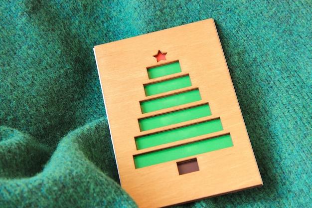 Kartka świąteczna wykonana z drewna z choinką na tle tekstylnym