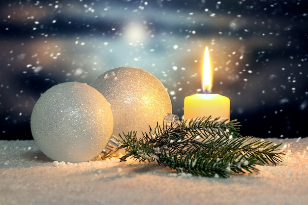 Kartka świąteczna z bombkami i świeczką na ciemnym tle podczas opadów śniegu