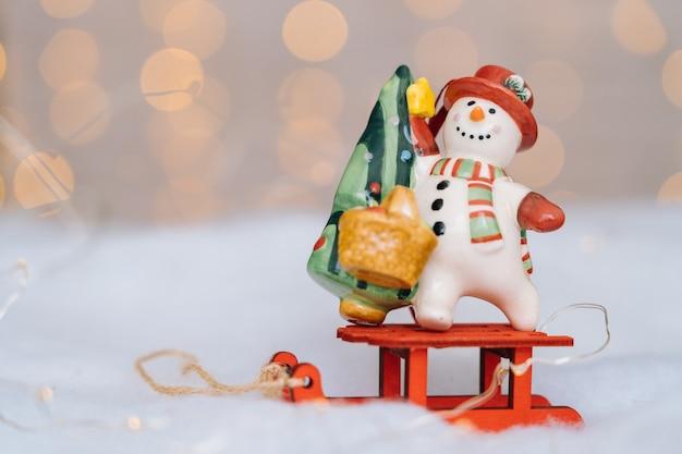Kartka świąteczna z czerwonymi drewnianymi saniami świętego mikołaja z człowiekiem śniegu