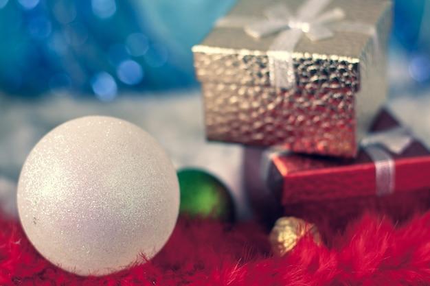 Kartka świąteczna z dużą białą kulą na pierwszym planie i pudełkami prezentowymi w tle. kolory czerwony, złoty i niebieski. bardzo płytkie skupienie na piłce, wszystko inne jest rozmyte.