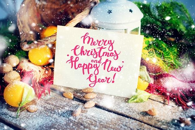 Kartka świąteczna z komunikatem wesołych świąt i szczęśliwego nowego roku. list, świerk, latarnia, mandarynki, orzechy na podłoże drewniane. zdobione rysunek płatki śniegu