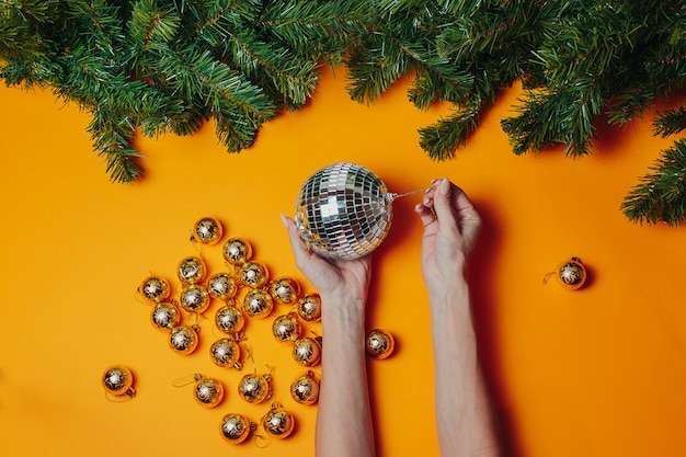 Kartka świąteczna z lato. kobieta trzyma ozdoby świąteczne na pomarańczowo. srebrna kula dyskotekowa w rękach z zielonymi gałązkami jodły wokół.
