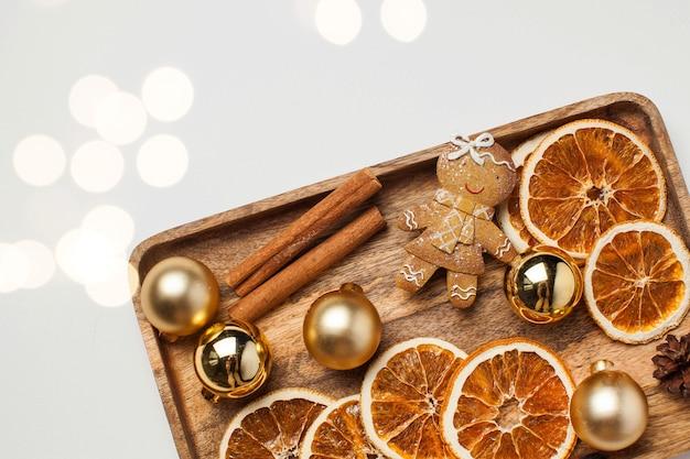 Kartka świąteczna z ludzikiem z piernika, cynamonem, suszonymi plasterkami pomarańczy i zabawkami świątecznymi