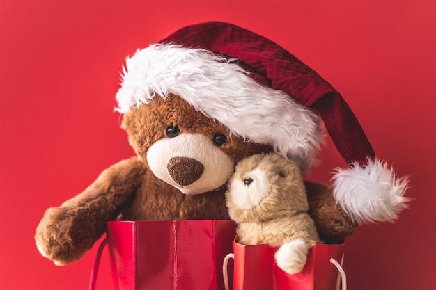 Kartka świąteczna z misiem i króliczkiem w czerwonych torebkach prezentowych.