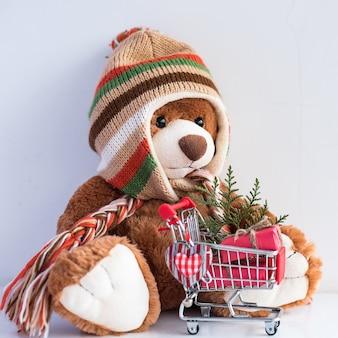 Kartka świąteczna z misiem i prezenty świąteczne w wózku w supermarkecie.