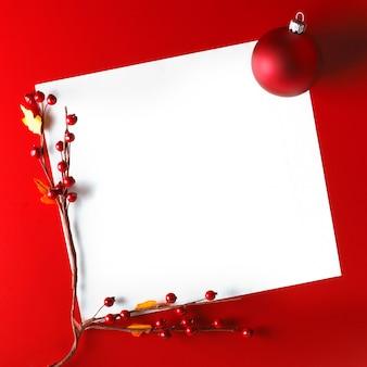 Kartka świąteczna z piłką i głogiem na czerwonym tle
