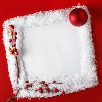 Kartka świąteczna z piłką, śniegiem i głogiem na czerwonym tle