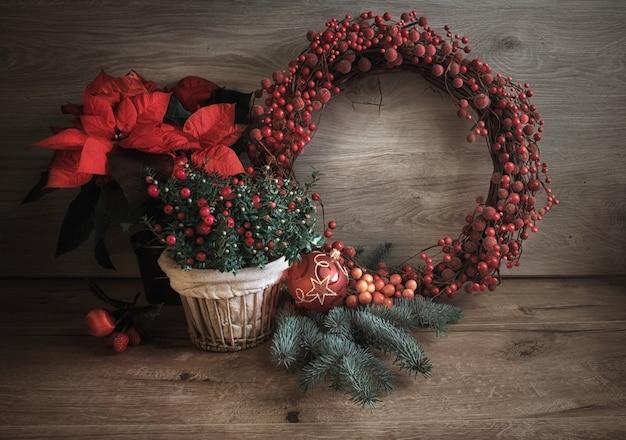 Kartka świąteczna z pozdrowieniami z czerwonymi i zielonymi dekoracjami na drewnie