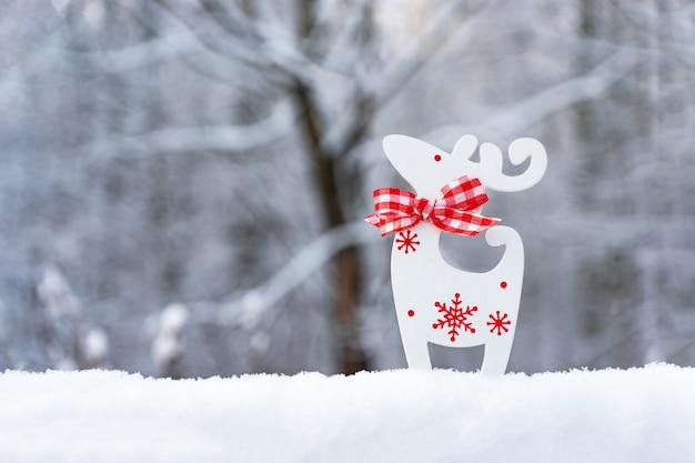 Kartka świąteczna ze śniegiem, płatki śniegu, biały jeleń na niewyraźne naturalne tło. szczęśliwego nowego roku, świąteczny nastrój. zimowe tło. skopiuj miejsce