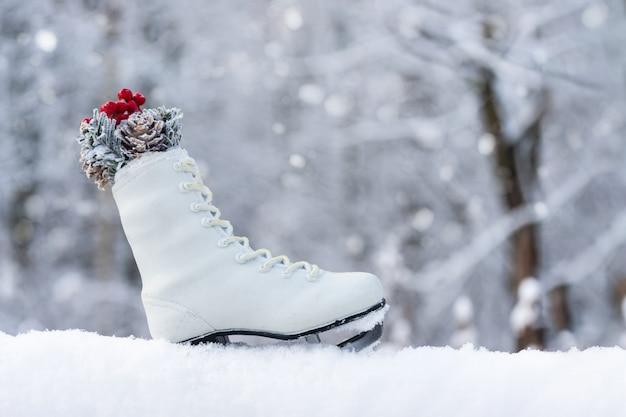 Kartka świąteczna ze śniegiem, płatki śniegu i łyżwy na niewyraźne naturalne tło. szczęśliwego nowego roku, świąteczny nastrój. zimowe tło. skopiuj miejsce